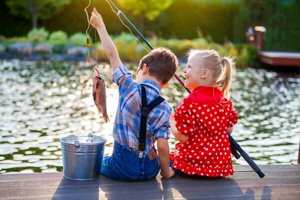 Little boy and girl fishing in a river