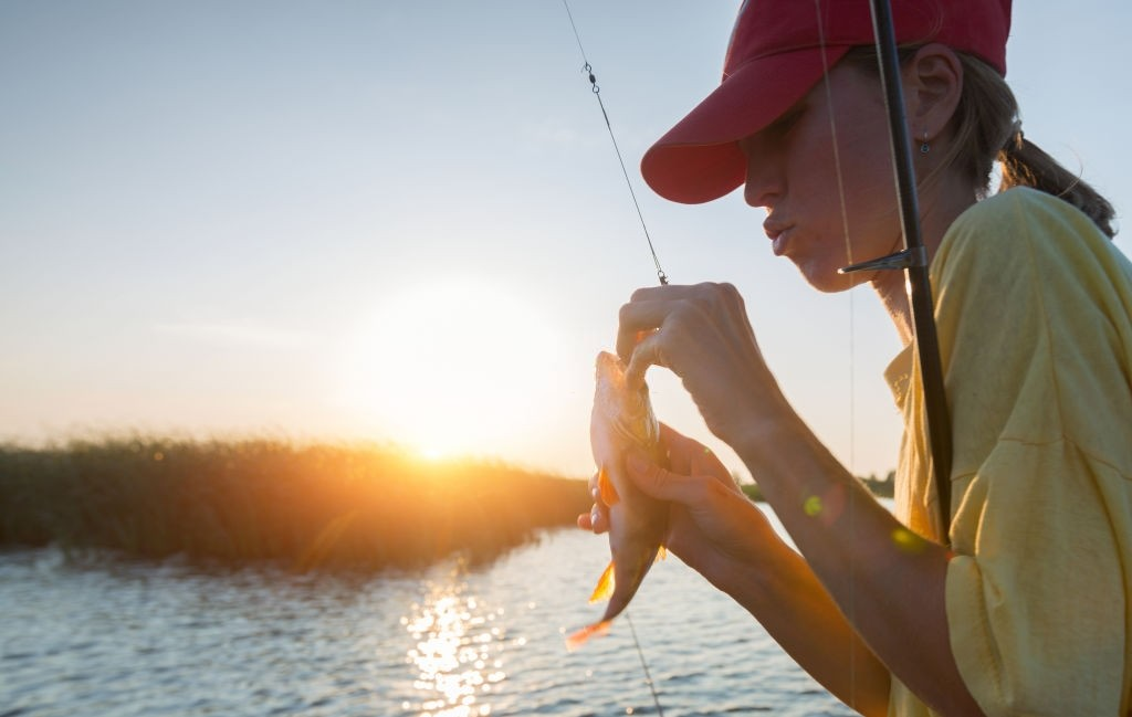 Young lady fishing perch on the river